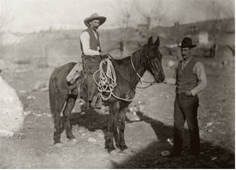Cowboy on a horse and man standing next to them